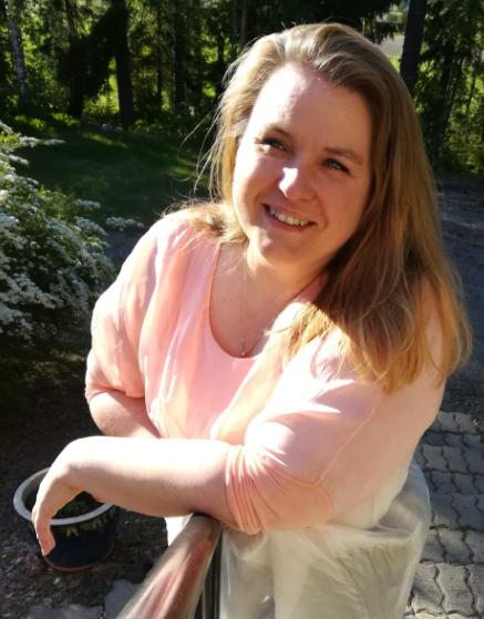 Pirita Eskola katsoo kesällä kameraan vaaleanpunaisessa paidassa